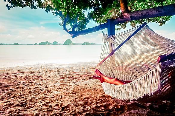Frau liegt in Hängematte am Strand