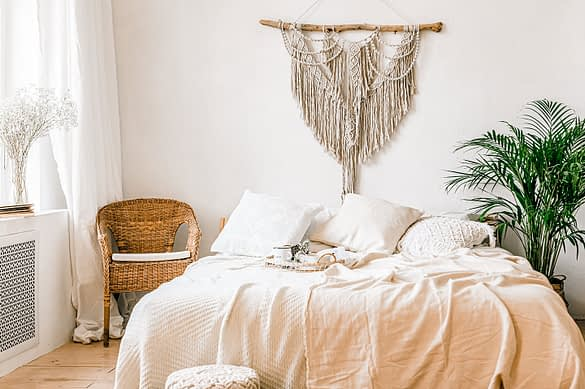 Schlafzimmer mit Bett und Makramee Wandschmuck